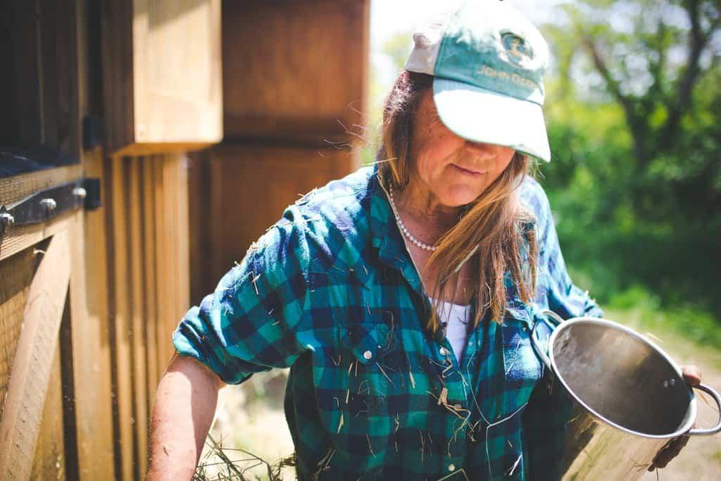 Cathy Payne, Block Island, Rhode Island farmer carries feed to farm animals