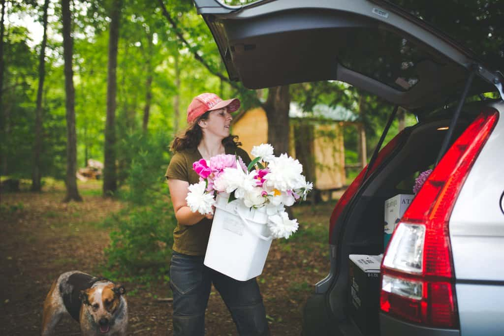 FarmHer Sarah Turkus loading a bucket of pick your own flowers into the back of a car.