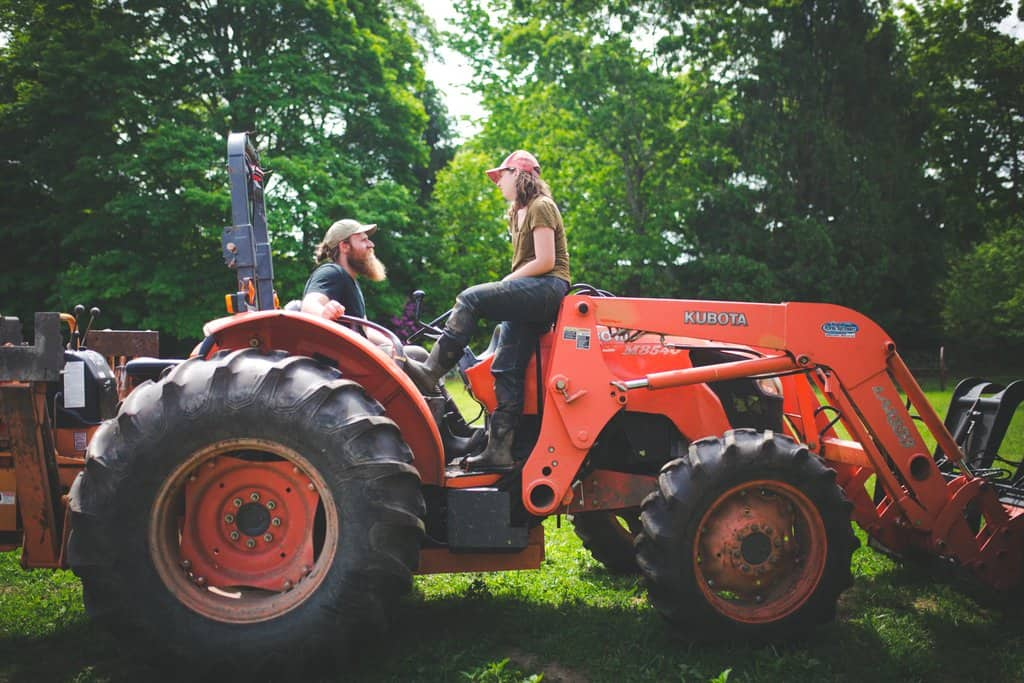 Farmers at Osamequin Farm on a Kubota utility tractor