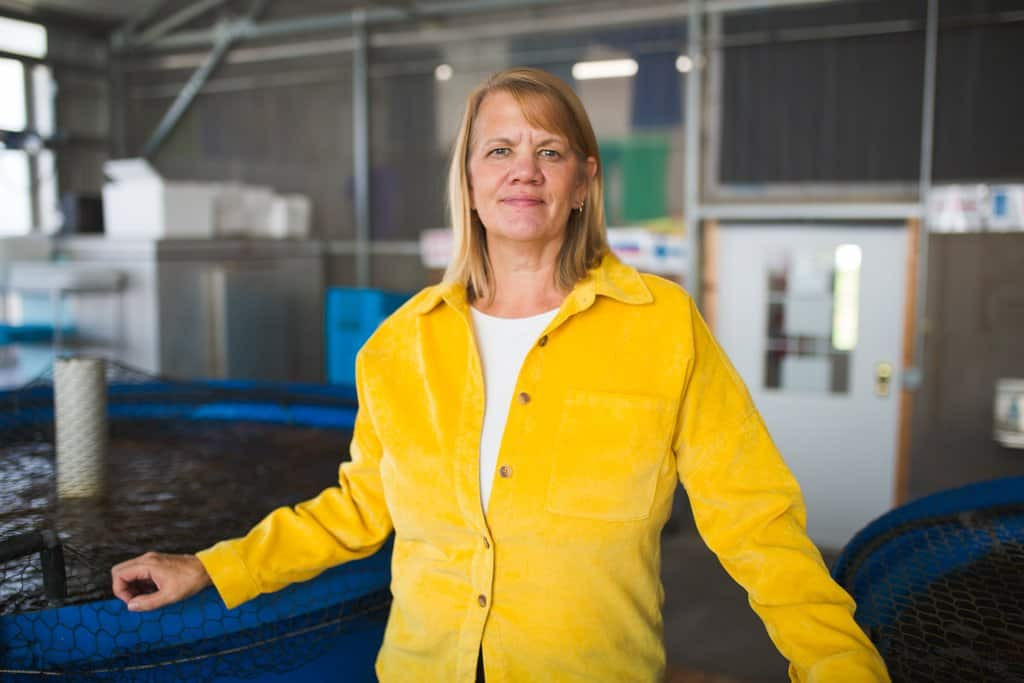 Rebecca Nelson stands in front of tilapia fish tanks at Nelson and Pade in Montello, Wisconsin