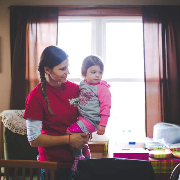 Farmher Anya Irons stands in house holding her little girl