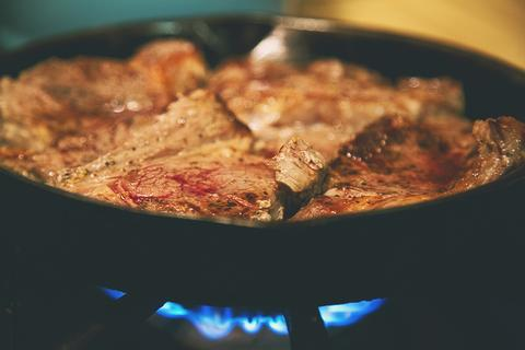 Meredith cooks a steak in their family's cast-iron skillet.