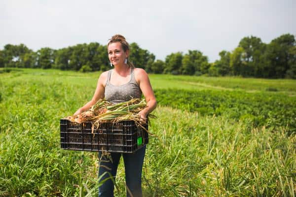 Lauren Rudersdorf, a millennial farmer carries crops through a field