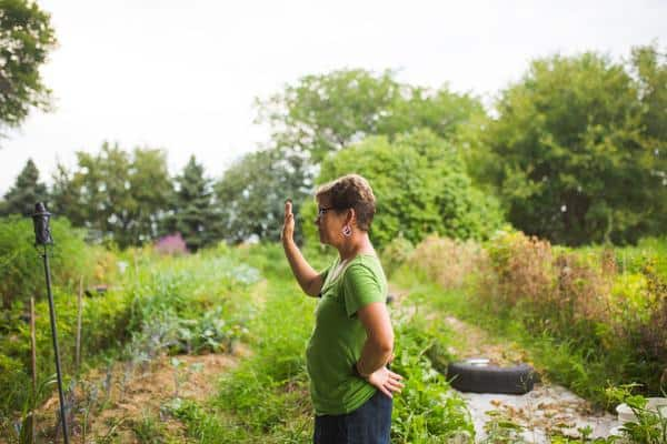 FarmHer Lisa Kivrist stands in a garden