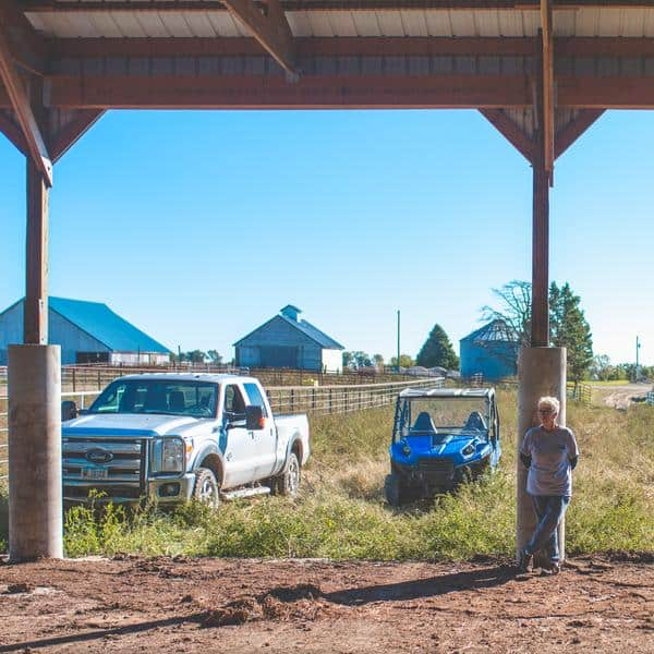 Farm woman stands in barn with Ford truck and blue side-by-side