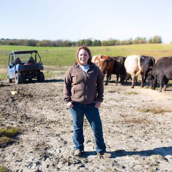 RanchHer stands in front of cattle in a pasture