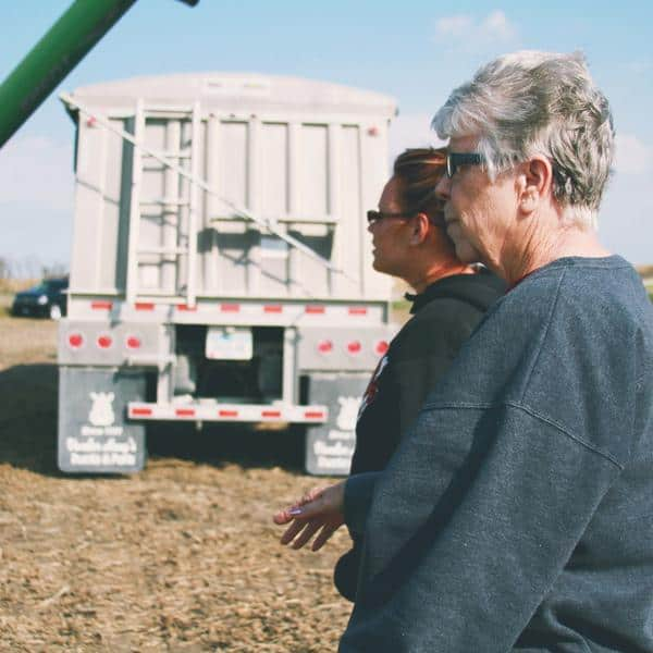 Farm women at harvest standing in front of a semi truck