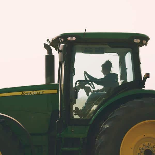 Woman driving John Deere tractor