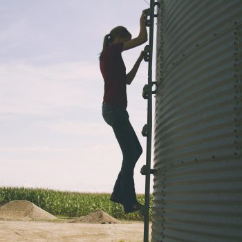 Marji Alaniz climbing a grain bin ladder with corn in the background.