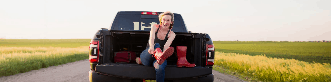 FarmHer Marji Alaniz in the back of a truck putting on red boots