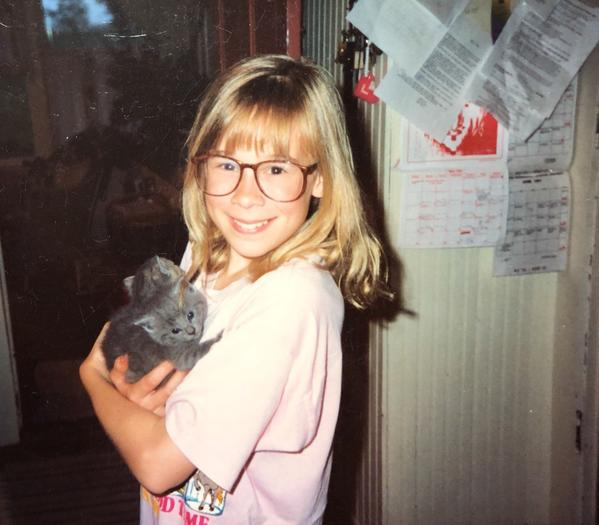 Young MARJI GUYLER-ALANIZ with barn kittens