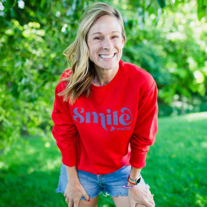 Marji shows the new red FarmHer SMILE crewneck sweatshirt
