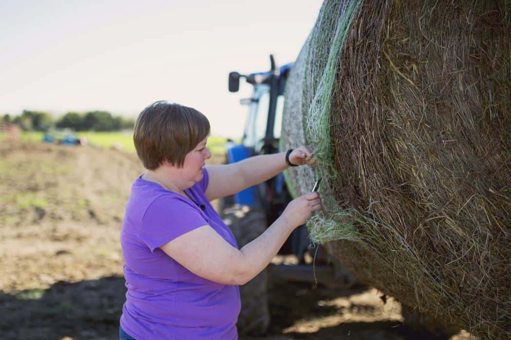 FarmHer Erin Cumings works with her husband to unload a bale of hay for their herd of cattle on their Iowa farm.