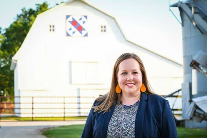 Erin Cumings balances a career at Nationwide with life on the farm. Here she stands on the farm in front of a white barn.