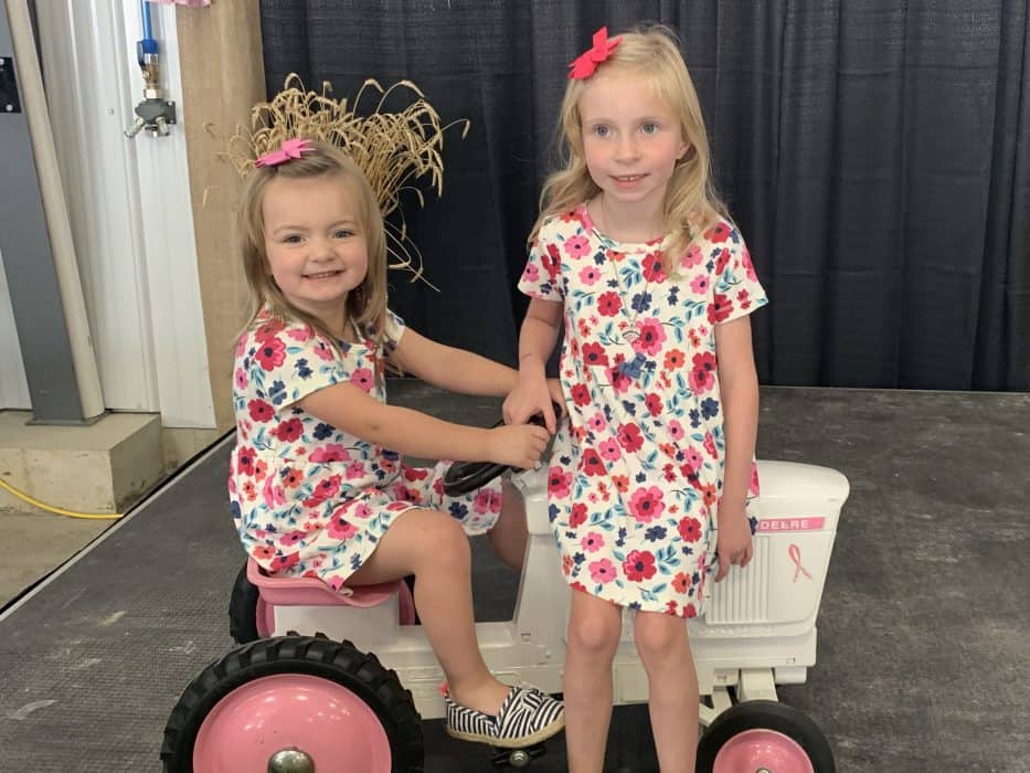 The Porteus grandaughters sit on a pink tractor at the cultivating a cure cancer fundraising event.