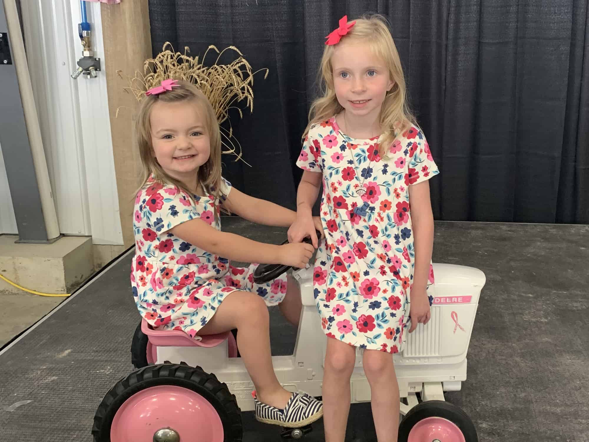 the porteus granddaughters sit on a tractor at their family's cultivating a cure event, raising funds for cancer and creating community