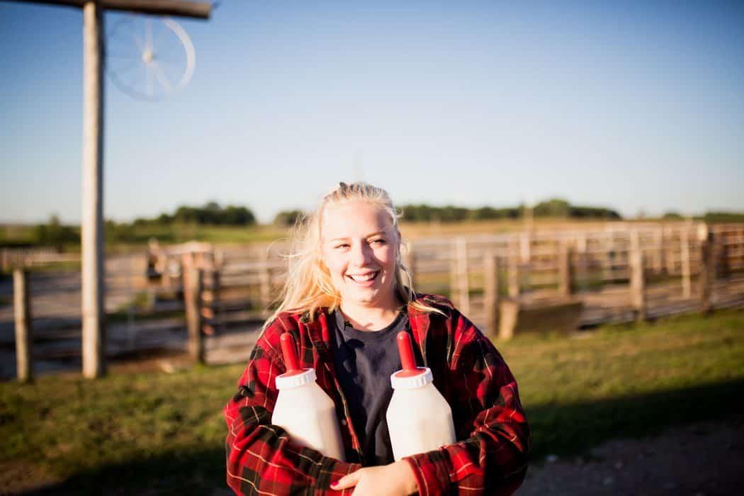 FarmHer Hannah Borg hold bottles for calves on her family farm