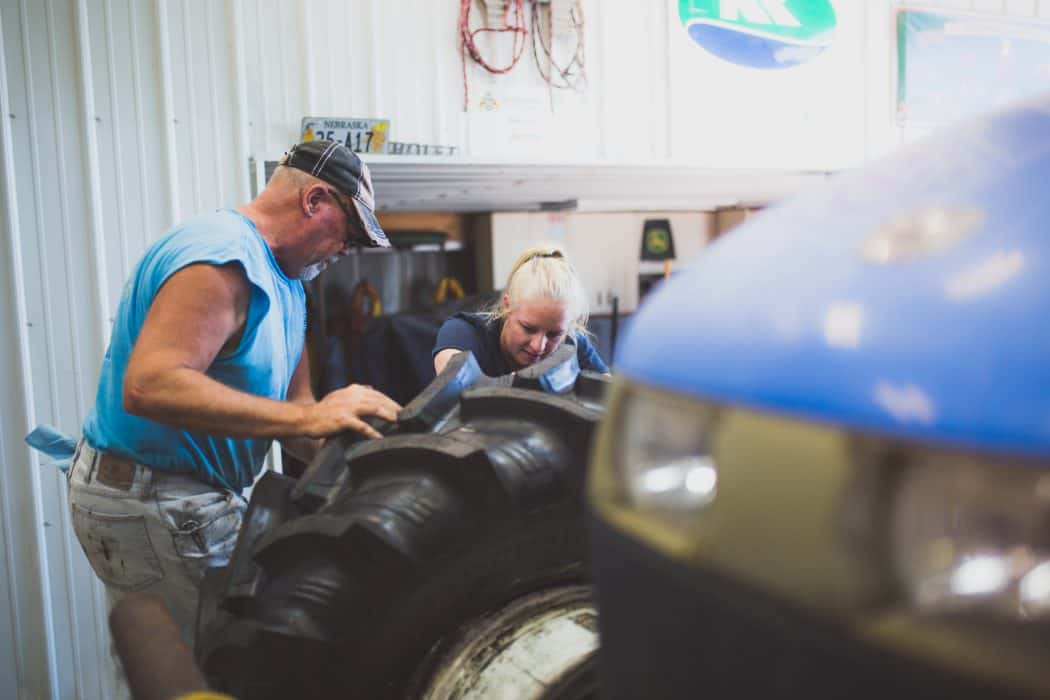 FarmHer Hannah Borg working on a tractor tire