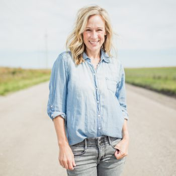 Marji Guyler-Alaniz stands on a gravel road in a denim shirt.