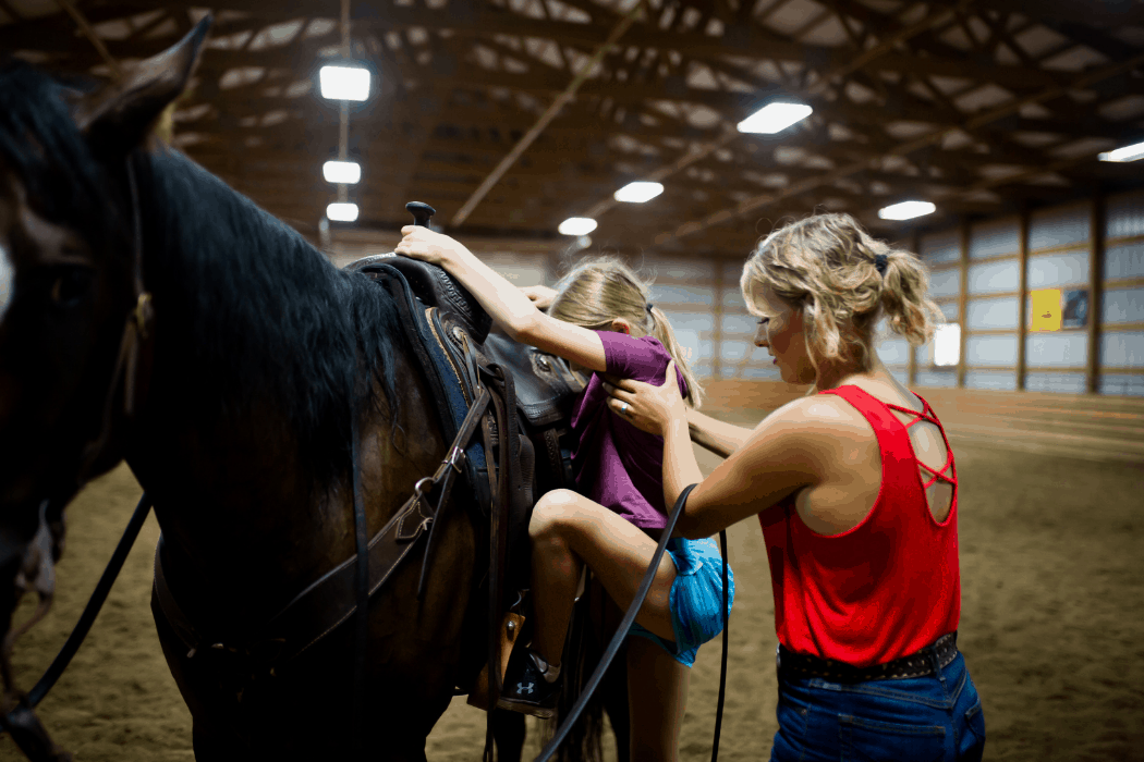 Sarah Eberspacher helps a student up on a horse for lessons.