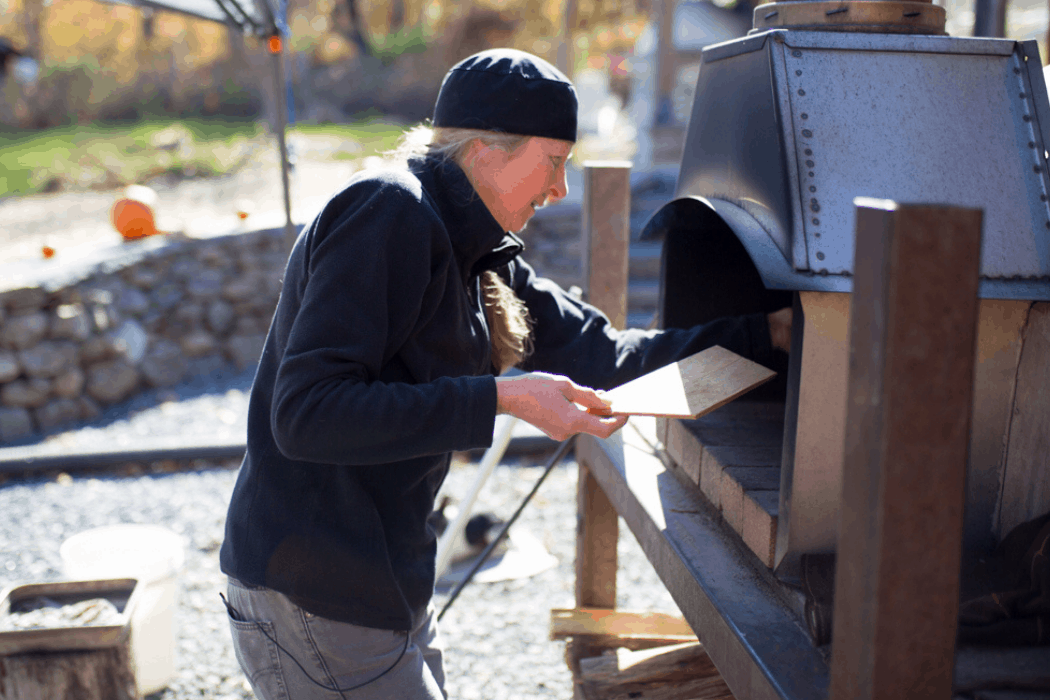 Chandra places a pizza in the wood-fire oven.