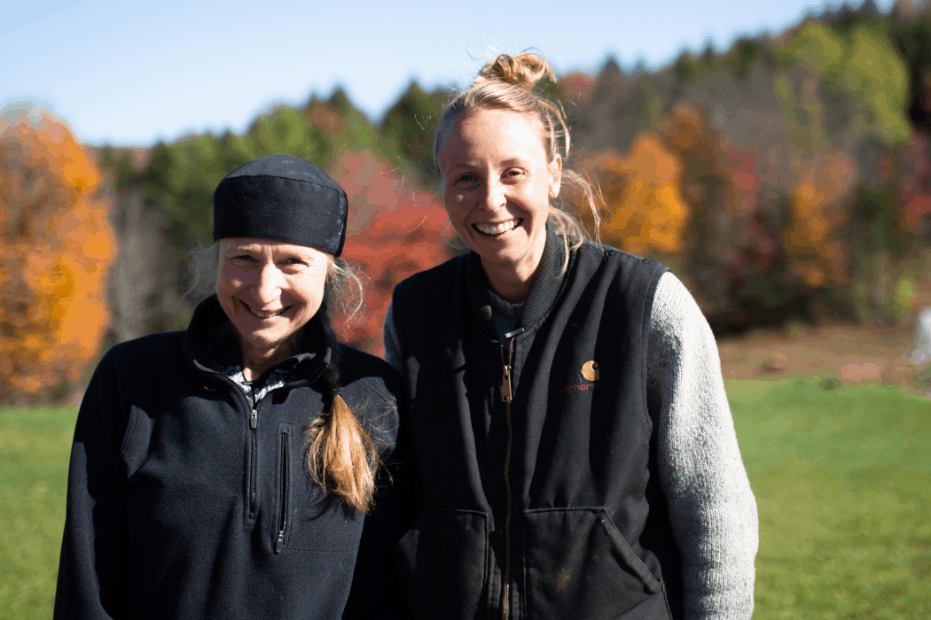 Chandra and Hannah stand in a field at their family farm in Vermont.