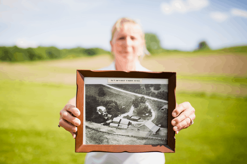 Sara Wyant holds an old photo of her family's farm in Iowa.