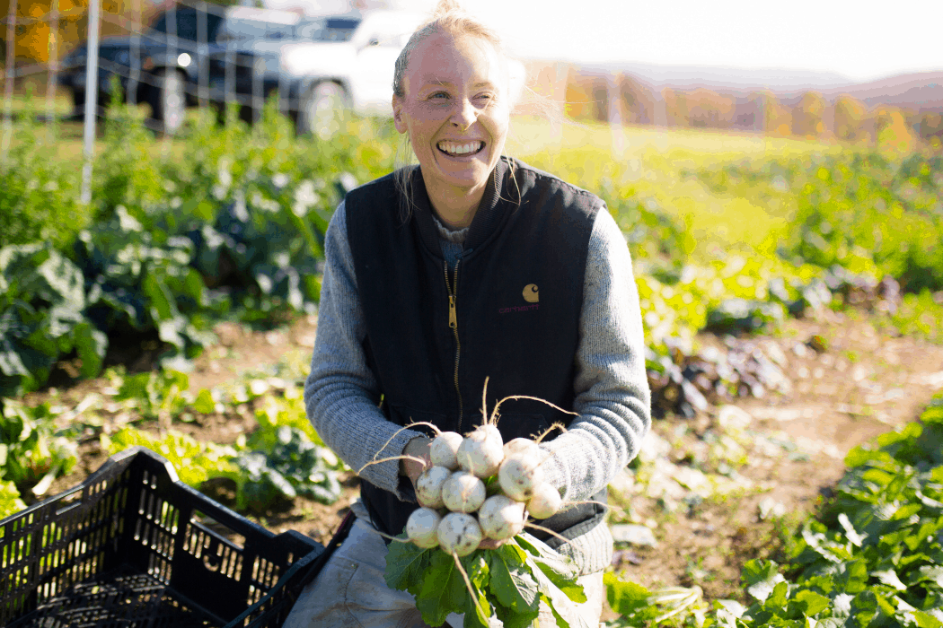 Hannah smiles, holding salad turnips fresh out of the field at their Vermont farm.