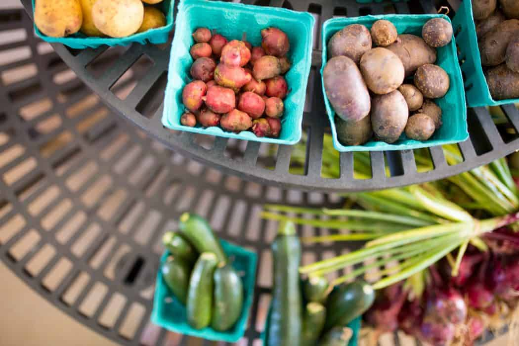 Blue boxes of potatoes, cucumbers, and radishes stacked on a black rack for donations to food banks.