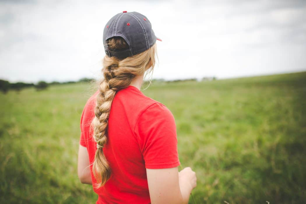 Woman with braid and hat in red tee shirt standing in field on Nebraska farm.