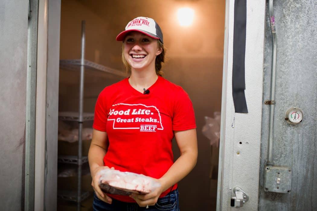 University of Nebraska Engler Entrepreneurship student Hannah Esch standing in a meat locker in a red tee shirt at her business Oak Barn Beef in Nebraska.