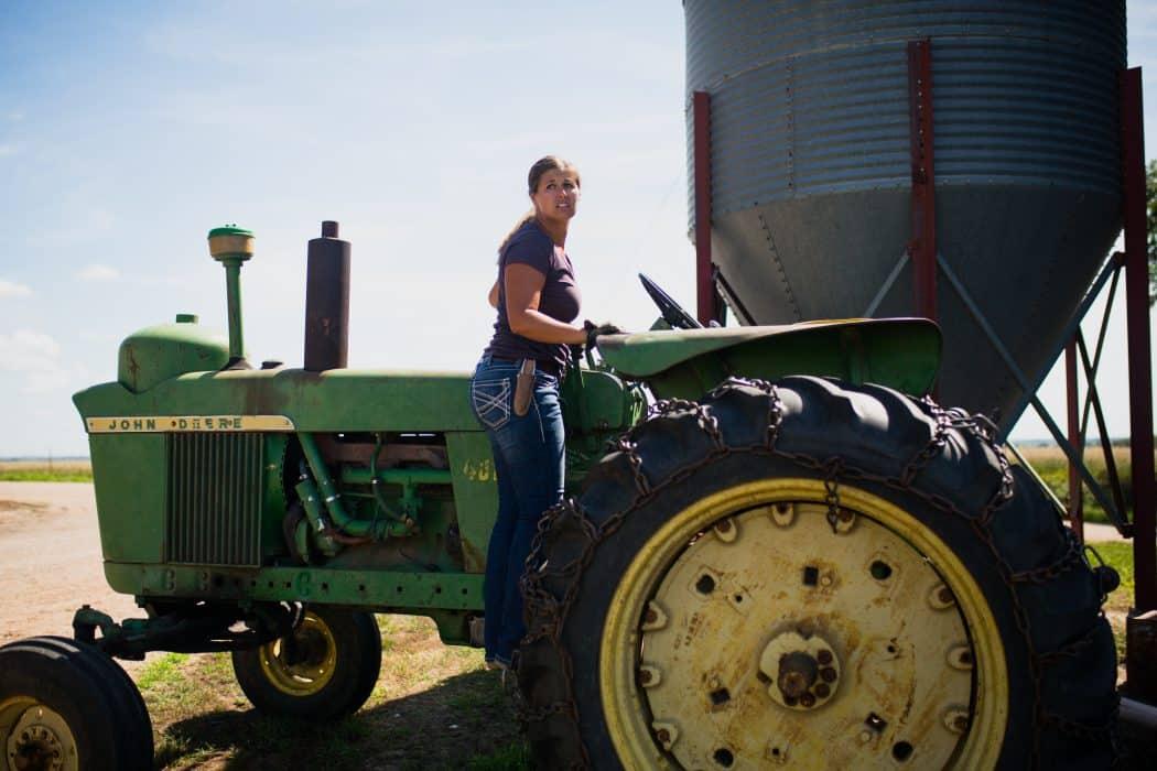 Woman standing on green John Deere older tractor on farm next to grain bin.