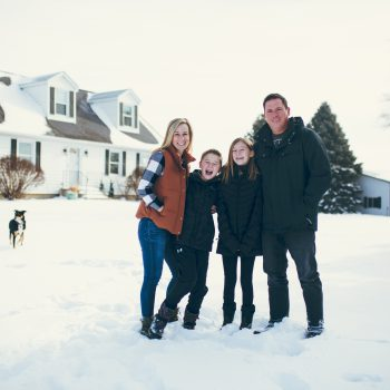 Family of four and farm dog stands in snow on farm with two story white house, white shop, and evergreen trees.