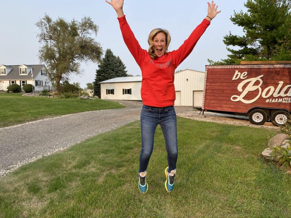 Woman in red sweatshirt jumping into the air with her hands up in front of her house and Be Bold FarmHer trailer.