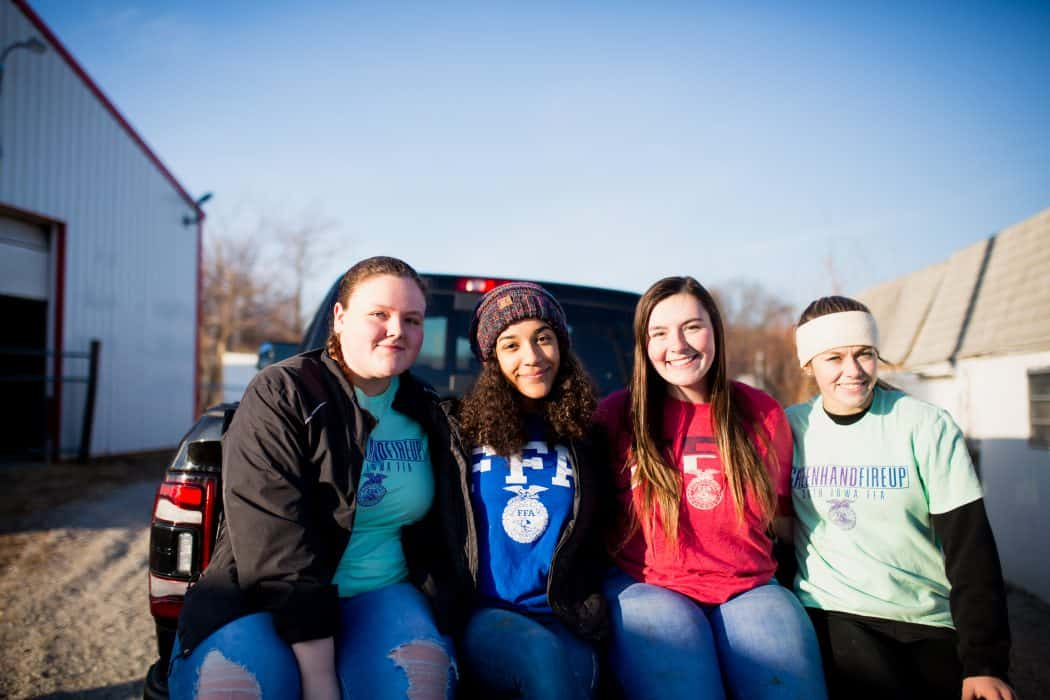 FFA members sitting on the back of a Ram pickup truck on a winter day.