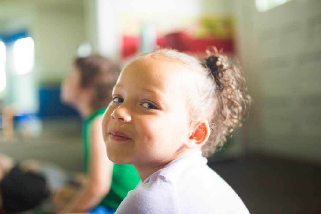 Young African American girl in preschool classroom smiling at camera.