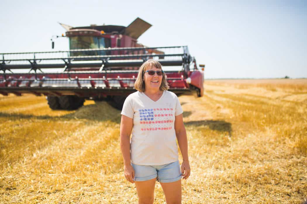 Woman standing in a freshly cut wheat field in front of a a CASE combine in a patriotic shirt.
