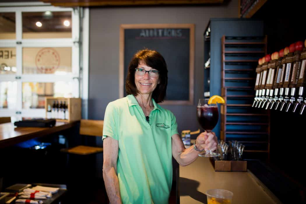 Deirdre Birmingham at The Cider Farm in Wisconsin in the tasting room holding a hard apple cider.