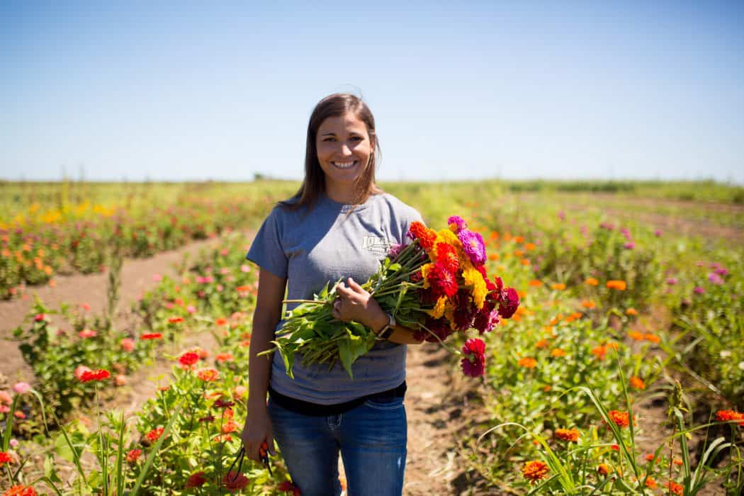 Woman standing in flower field holding fresh picked red, yellow, and purple flowers grown on her family farm.