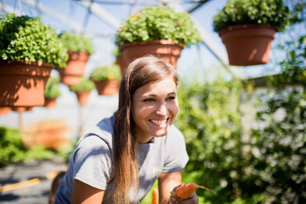 Woman smiling and standing in greenhouse where fresh produce is grown.
