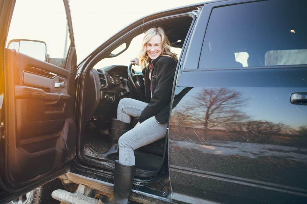 Marji Guyler-Alaniz in a RAM pickup truck at sunset.