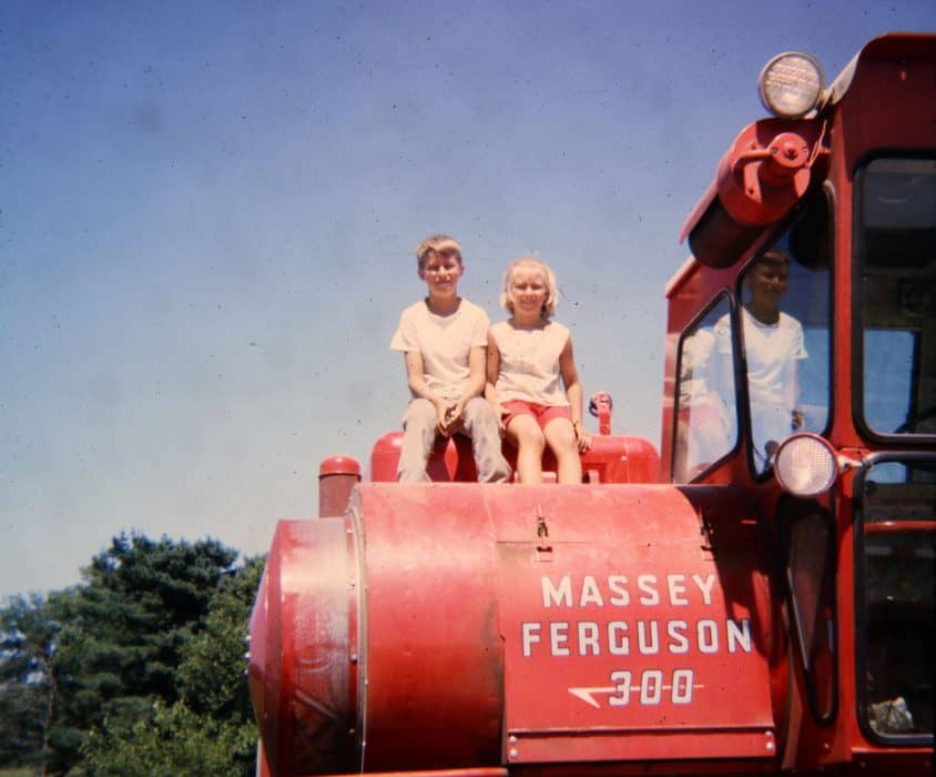 Sara Wyant and sibling sitting on a Massey Ferguson 300 tractor on their family farm.
