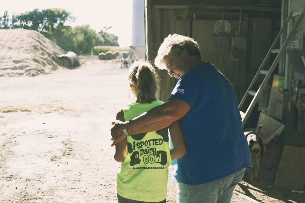 Older woman hugging and giving advice to younger girl on the farm in a barn.