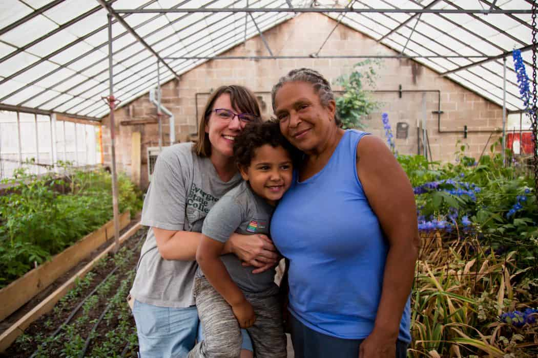 Two women and a child stand in green house at a urban farm.