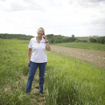 Sara Wyant, creator of Agri-Pulse and media journalist standing on her century farm.