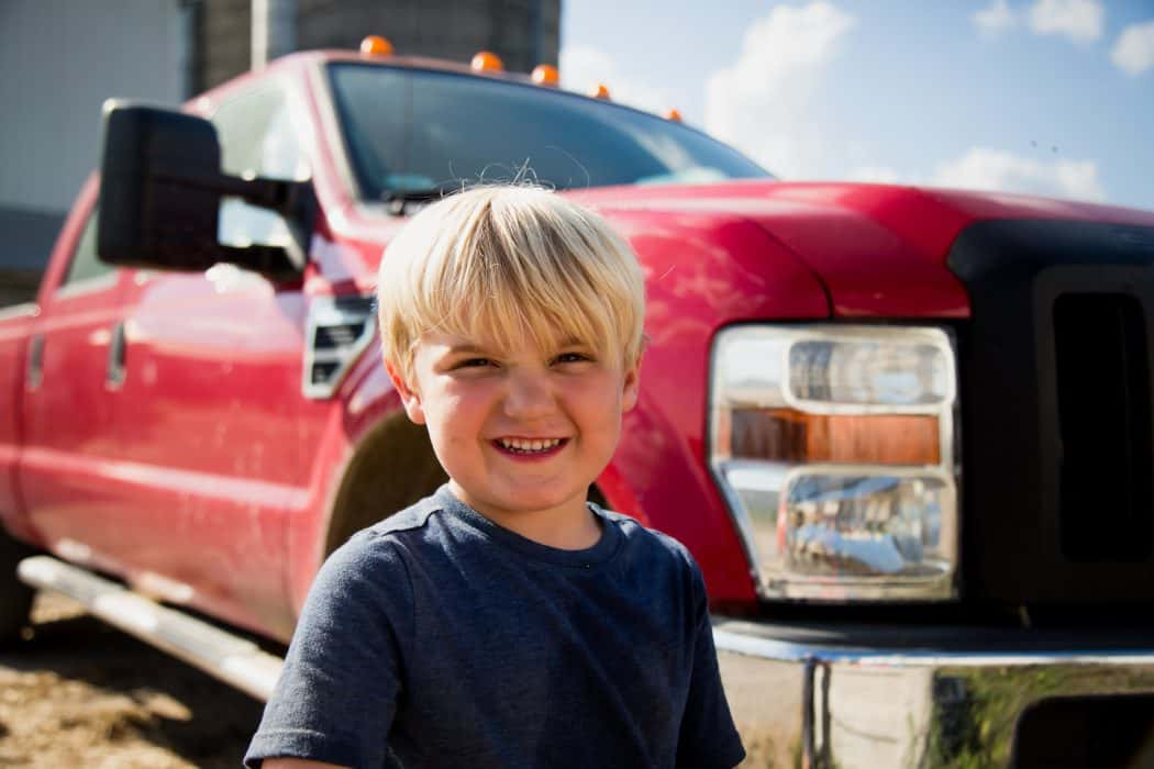 Young blonde boy standing in front of a red Ford pickup truck.