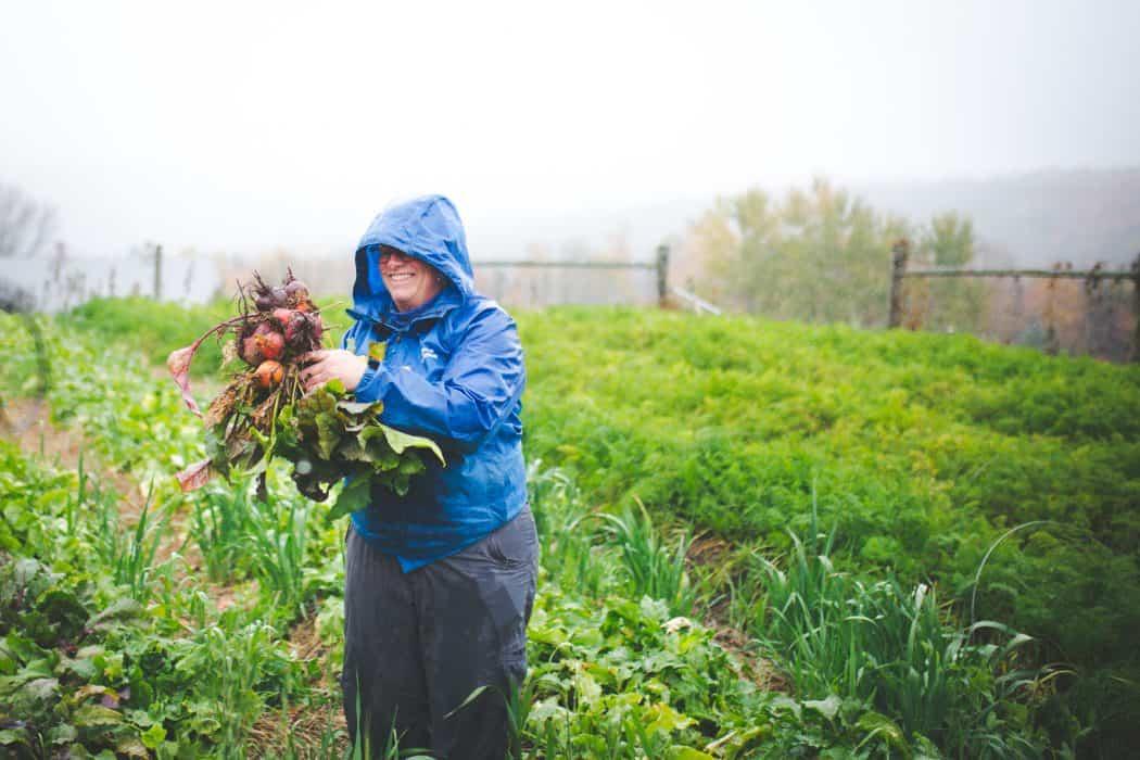 Mari from Green Mountain Girls Farm standing in the rain in her vegetable garden holding vegetables.