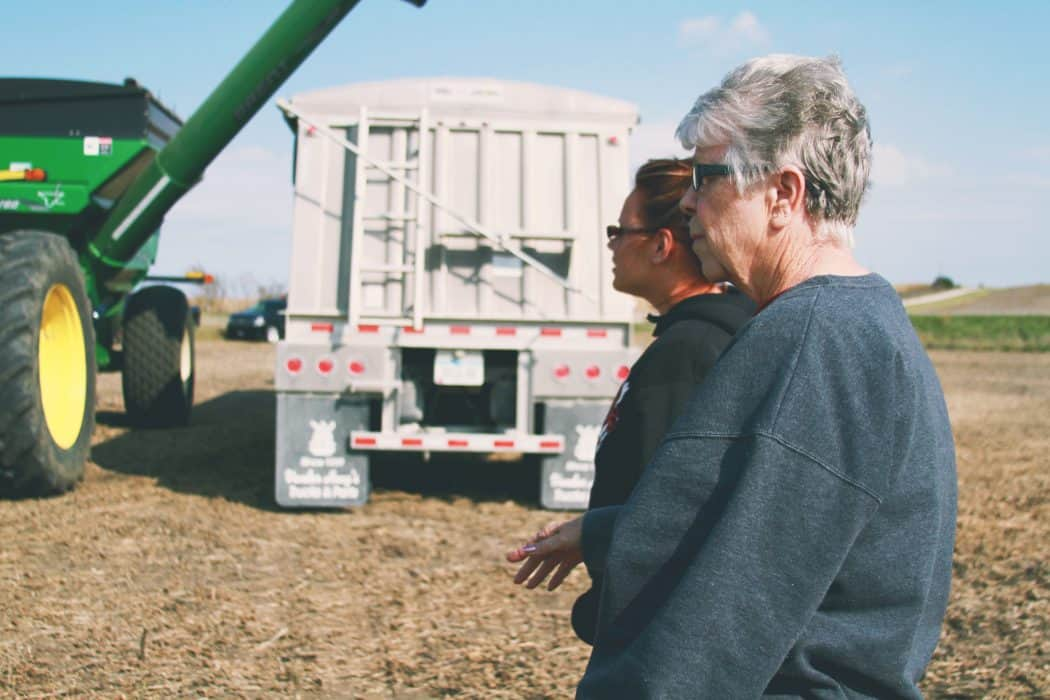 Two women standing in a harvest field looking at John Deere grain cart and semi- truck trailer.