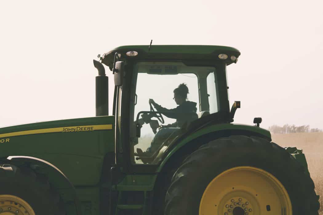 Woman driving John Deere tractor in field.
