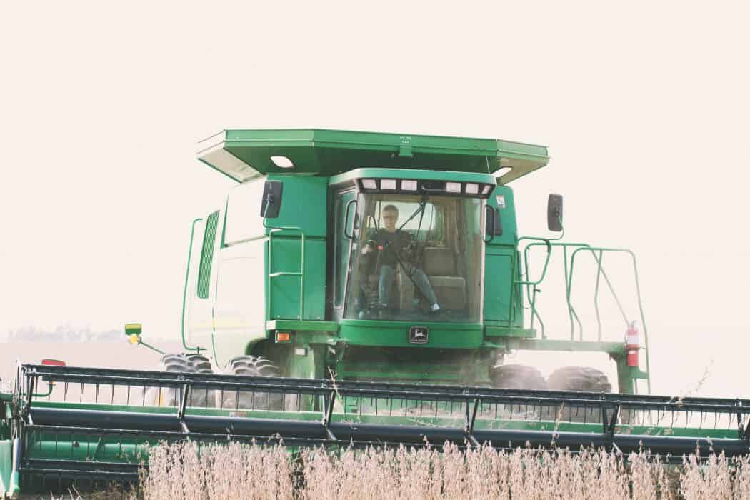 Woman driving John Deere combine on community harvest day for a local farmer.